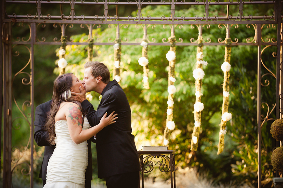 Bride and groom kissing during ceremony under garlands.