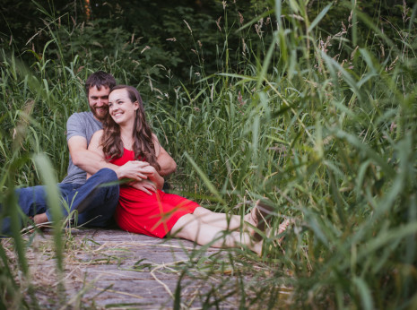 couple sitting on boardwalk surrounded by grass