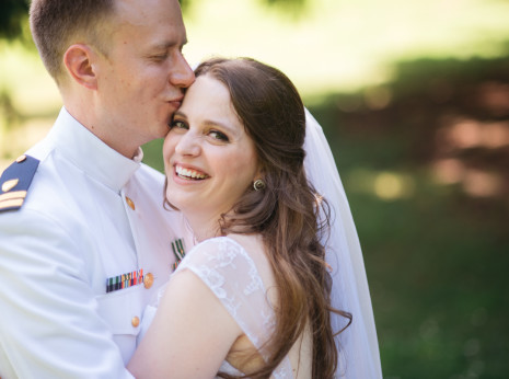 Coast Guard uniformed groom with laughing bride
