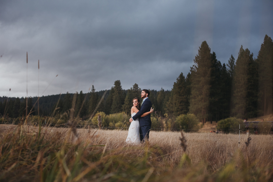 Bride & Groom in mountain meadow under storm clouds